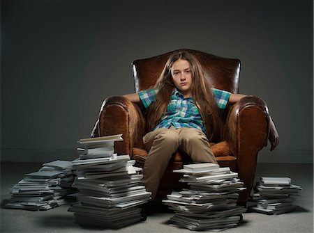 Girl sitting in leather armchair with piles of books Stock Photo - Premium Royalty-Free, Code: 649-06812233