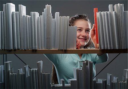 selecting - Girl choosing red book from bookshelf Stock Photo - Premium Royalty-Free, Code: 649-06812246