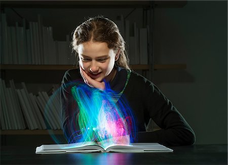 Girl reading book with multicoloured lights Stock Photo - Premium Royalty-Free, Code: 649-06812247