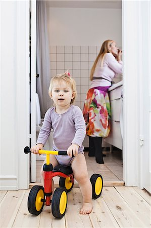 Toddler girl playing on tricycle, mother in background Stock Photo - Premium Royalty-Free, Code: 649-06812252