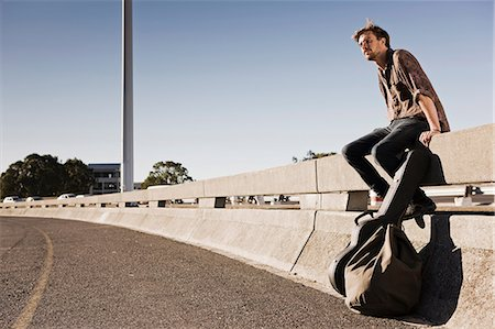 Young man waiting for a ride at the side of a road Stock Photo - Premium Royalty-Free, Code: 649-06812349