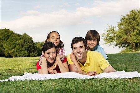 Portrait of family with two children lying on grass Stock Photo - Premium Royalty-Free, Code: 649-06812447