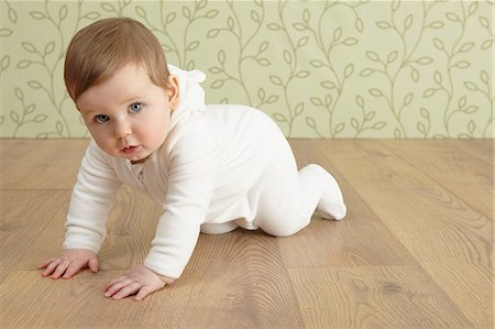 Baby girl crawling on floor Stock Photo - Premium Royalty-Free, Code: 649-06812525