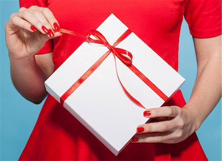 red - Woman opening white gift box with red bow, mid section Stock Photo - Premium Royalty-Free, Code: 649-06812641