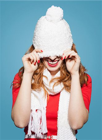 pulling - Woman pulling white bobble hat over eyes Stock Photo - Premium Royalty-Free, Code: 649-06812654