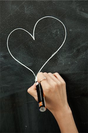 Young woman drawing heart on blackboard Stock Photo - Premium Royalty-Free, Code: 649-06812756