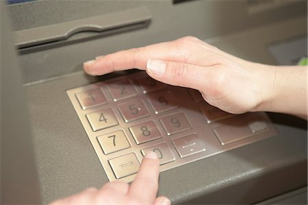 purchase - Woman covering keypad when entering PIN in cashpoint Stock Photo - Premium Royalty-Free, Code: 649-06812924
