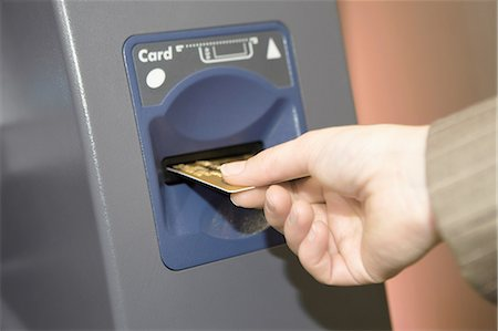 Woman inserting credit card into cashpoint Stock Photo - Premium Royalty-Free, Code: 649-06812927