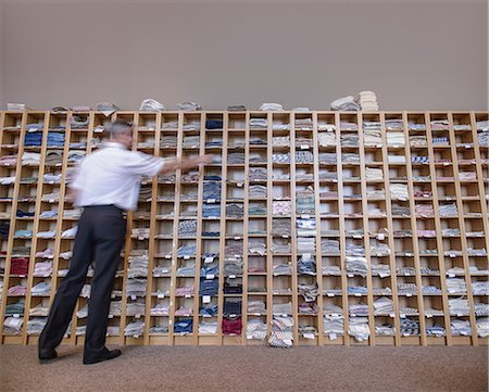 Man selecting fabric samples from shelving unit Stock Photo - Premium Royalty-Free, Code: 649-06812953