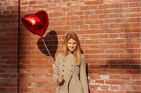 Woman with red heart-shaped balloon Stock Photo - Premium Royalty-Free, Code: 649-06813027