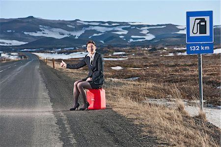 Woman sitting on petrol can at roadside hitchhiking Stock Photo - Premium Royalty-Free, Code: 649-06813071
