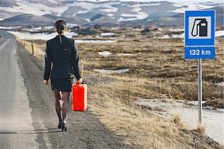 road landscape - Woman walking down road carrying petrol can Stock Photo - Premium Royalty-Free, Code: 649-06813072