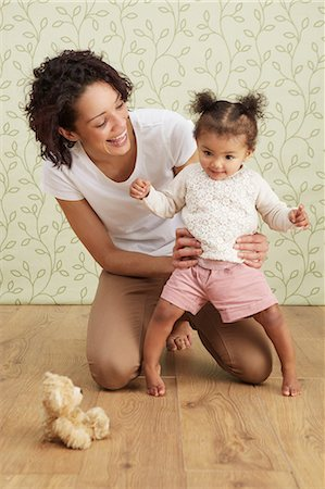 Mother holding baby girl taking first steps, smiling Stock Photo - Premium Royalty-Free, Code: 649-06829434