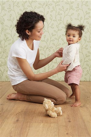 Mother holding baby girl taking first steps Stock Photo - Premium Royalty-Free, Code: 649-06829435