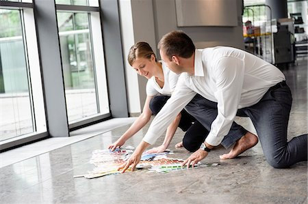 Young woman and mid adult man arranging swatches on lobby floor Stock Photo - Premium Royalty-Free, Code: 649-06829454