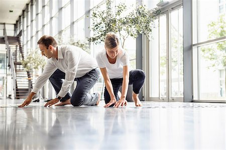 Young woman and mid adult man arranging swatches on lobby floor Stock Photo - Premium Royalty-Free, Code: 649-06829452