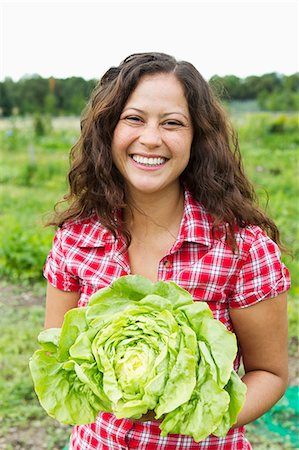 Portrait of young woman holding cabbage in allotment Stock Photo - Premium Royalty-Free, Code: 649-06829478