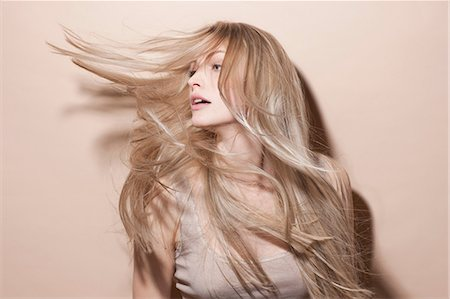 Young blonde woman flicking hair Stock Photo - Premium Royalty-Free, Code: 649-06829549