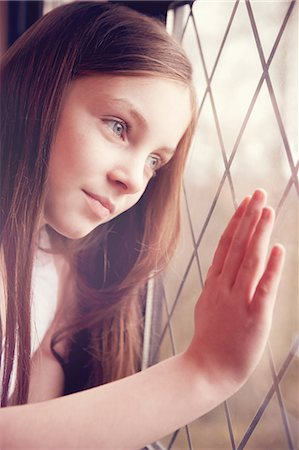 preteen touch - Young girl looking though window Stock Photo - Premium Royalty-Free, Code: 649-06829586