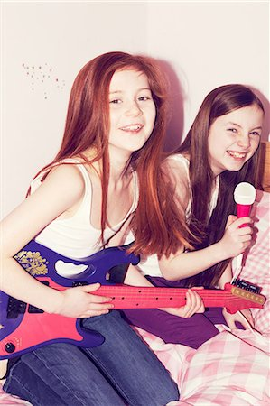 Two girls playing guitar and singing into microphone in bedroom Stock Photo - Premium Royalty-Free, Code: 649-06829588
