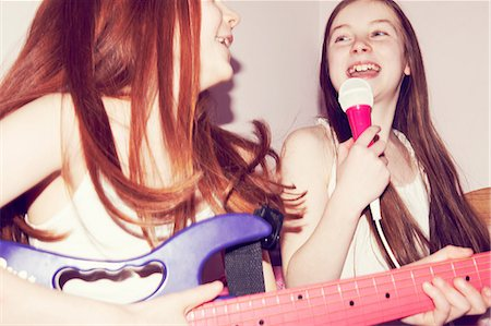 Two girls playing guitar and singing into microphone in bedroom Stock Photo - Premium Royalty-Free, Code: 649-06829589