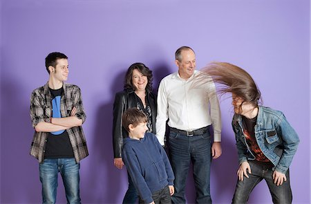 Family watching son headbang in front of purple background Stock Photo - Premium Royalty-Free, Code: 649-06829582