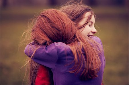 red hair preteen girl - Young friends embracing outdoors Stock Photo - Premium Royalty-Free, Code: 649-06829592