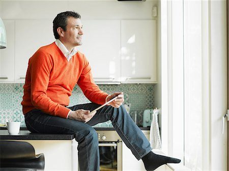sweater - Mature man holding tablet and sitting on kitchen worktop Stock Photo - Premium Royalty-Free, Code: 649-06829607