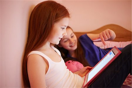 red hair preteen girl - Girls using digital tablet together in bedroom Stock Photo - Premium Royalty-Free, Code: 649-06829603