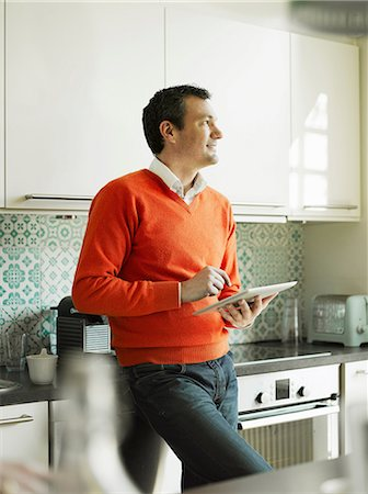 Mature man using tablet in kitchen Stock Photo - Premium Royalty-Free, Code: 649-06829610