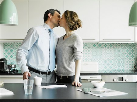 Mid adult woman kissing businessman in kitchen Stock Photo - Premium Royalty-Free, Code: 649-06829628