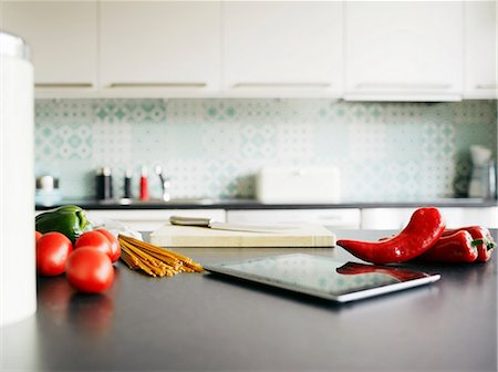 Digital tablet, red peppers and tomatoes on kitchen counter Stock Photo - Premium Royalty-Free, Code: 649-06829620
