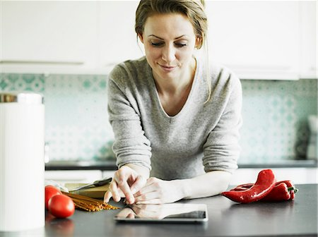 Mid adult woman using digital tablet on kitchen counter Stock Photo - Premium Royalty-Free, Code: 649-06829621