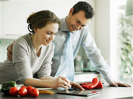 Businessman and wife using digital tablet in kitchen Stock Photo - Premium Royalty-Free, Code: 649-06829623