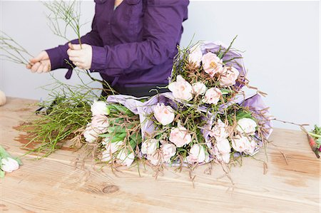 Close up of young florist arranging plants and roses into bouquet Stock Photo - Premium Royalty-Free, Code: 649-06829663