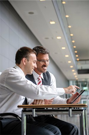 Two businessmen looking and pointing at digital tablet Stock Photo - Premium Royalty-Free, Code: 649-06829814