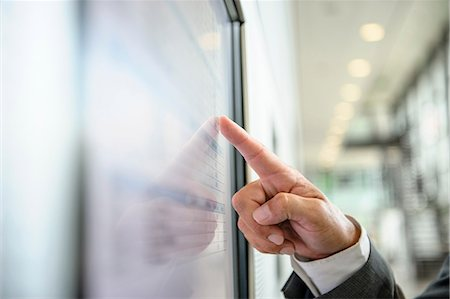 Close up of hand pointing at wall screen Stock Photo - Premium Royalty-Free, Code: 649-06829819