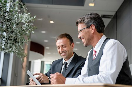 partnership - Two businessmen looking at digital tablet Stock Photo - Premium Royalty-Free, Code: 649-06829813