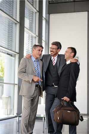 Three businessmen talking and laughing Stock Photo - Premium Royalty-Free, Code: 649-06829832
