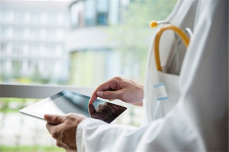 Close up of young male doctor using digital tablet Stock Photo - Premium Royalty-Free, Code: 649-06829844