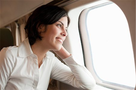 Candid portrait of young female looking out of aeroplane window Stock Photo - Premium Royalty-Free, Code: 649-06829853