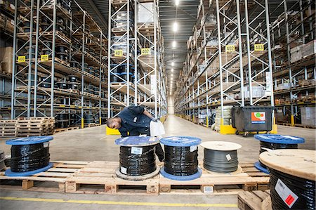 Male warehouse worker checking pallet order Stock Photo - Premium Royalty-Free, Code: 649-06829923