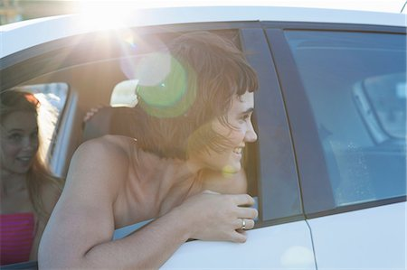 road trip - Woman looking over shoulder through car window Stock Photo - Premium Royalty-Free, Code: 649-06829955