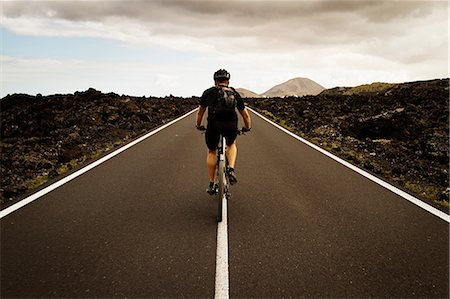 Man mountain biking on road, Lanzarote Stock Photo - Premium Royalty-Free, Code: 649-06829974
