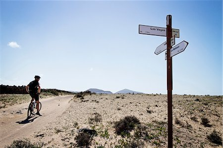 Man mountain biking past sign post, Lanzarote Stock Photo - Premium Royalty-Free, Code: 649-06829975