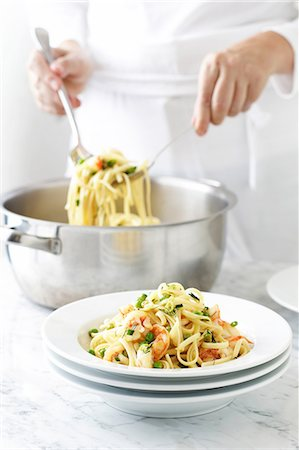Woman serving linguine Stock Photo - Premium Royalty-Free, Code: 649-06830043