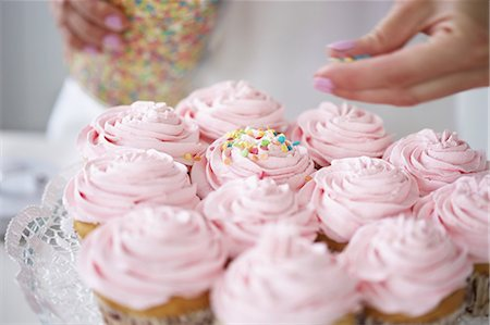 Woman decorating cupcakes with sugar sprinkles Stock Photo - Premium Royalty-Free, Code: 649-06830177
