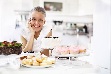 Portrait of woman with selection of hand made cakes Stock Photo - Premium Royalty-Free, Code: 649-06830180