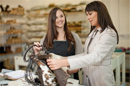 Customer and shop assistant looking at leather bag Stock Photo - Premium Royalty-Free, Code: 649-06844086