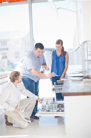 purchase - Couple and salesman looking at dishwasher in kitchen showroom Stock Photo - Premium Royalty-Free, Code: 649-06844106